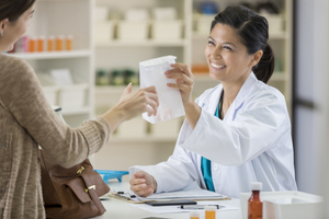 Beautiful Asian female pharmacist assists customer